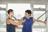 Young man exercising with his personal trainer in the gym — Foto Stock