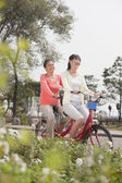 Grandmother and granddaughter riding tandem bicycle — Stock Photo