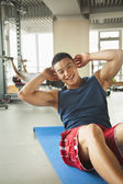 Young man doing sit-ups in the gym — Stockfoto