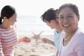 Family on the beach, starfish — Stock Photo