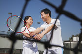 Young girl playing tennis with her coach — Stock Photo