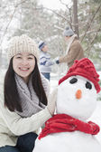 Mother making snowman in winter — Stock Photo