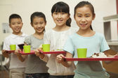 Row of students standing in line in school cafeteria — Stock Photo