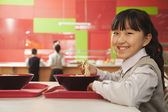 School girl eating noodles — Stock Photo