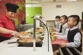School children standing in line in school cafeteria — Stock Photo