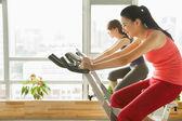 Mujeres jóvenes en bicicletas fijas, hacer ejercicio en el gimnasio — Foto de Stock