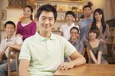 コーヒー ショップでお友達のグループと若い男の肖像 — ストック写真