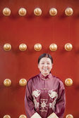 Woman next to traditional Chinese door — Stock Photo