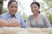 Mature women playing Chinese checkers — Stock Photo
