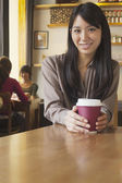 Woman holding coffee cup — Stock Photo