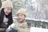 Mother helping son make snow ball — Stock Photo
