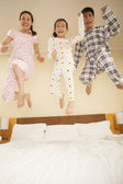 Family Jumping on Bed Together — Stock Photo