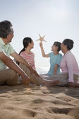 Family sitting on the beach looking at starfish — Stock Photo