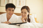 Young Couple Using Tablet in Bed — Stok fotoğraf