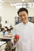 Chef in school cafeteria holding apple — Stock Photo