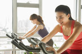在健身房里锻炼的固定自行车上的年轻女性 — 图库照片