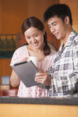 Young Couple Using Tablet in Kitchen — Stock Photo