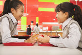 Girls talk over lunch in school cafeteria — Stock Photo