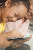 Granddaughter playing on digital tablet with grandfather — Stock Photo