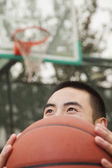 Young man with a basketball on the basketball court — Stock Photo