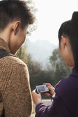 Young couple smiling, woman holding digital camera — Stock Photo