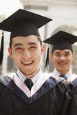 Jóvenes graduados en toga y birrete — Foto de Stock
