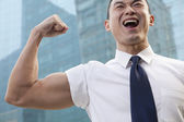 Young businessman flexing muscle — Stok fotoğraf