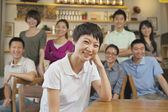 Portrait of young woman with group of friends at a coffee shop — Stockfoto