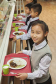 School children standing in line in school cafeteria — Stock Photo