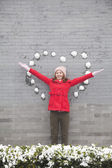 Woman on wall with heart shaped snow balls — Stock Photo