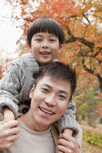 Father and son smiling in the park in autumn — Stock Photo