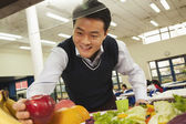 Teacher reaching for healthy food in school cafeteria — Stock Photo