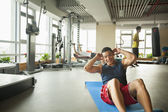 Young man doing sit-ups in the gym — 图库照片