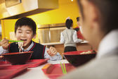 School boy eating noodles in school cafeteria — Stock Photo