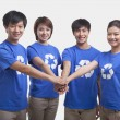 People in recycling t-shirts with hands together — Stock Photo