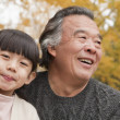 Grandfather and granddaughter in park — Stock Photo #36347443