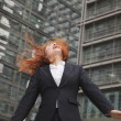 Businesswoman looking up with wind blowing in her hair — Stock Photo
