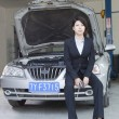 Businesswoman Sitting on Car With Open Hood — Stock Photo #36349393