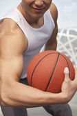 Man showing bicep and holding basketball — Stock Photo