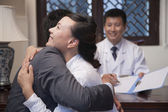 Patient and Spouse Hug at the Good News — Photo