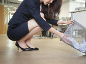 Businesswoman looking through wastepaper bin — Stock Photo