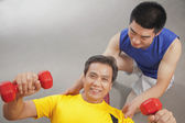Mature man working out with weights — Stock Photo
