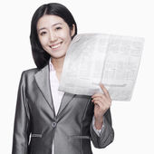 Businesswoman standing with newspaper — Stock Photo