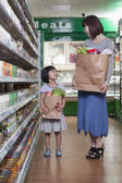 Mother and daughter in supermarket — Stok fotoğraf