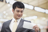 Business man looking at flight ticket — Stock Photo