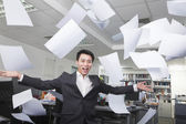 White-collar worker throwing white sheets in air in office — Stock Photo