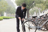 Businessman locking up his bicycle — Stock Photo