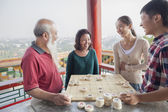 Chinese Family Playing Chinese Chess (Xiang Qi) — Stock Photo