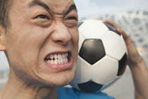 Angry young man holding a soccer ball — Stock Photo