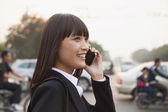 Businesswoman using the phone on the street — Stock Photo